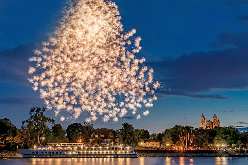 Feuerwerke über dem Rhein mit einem Schiff und der Kathedrale in Speyer in Deutschland stockfotografie