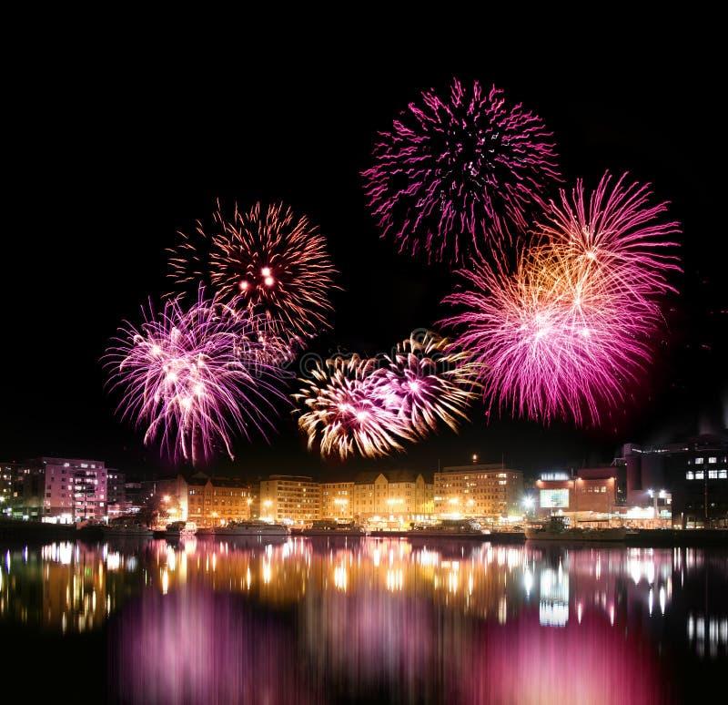 Feuerwerke über Stadt durch das Wasser stockfotografie