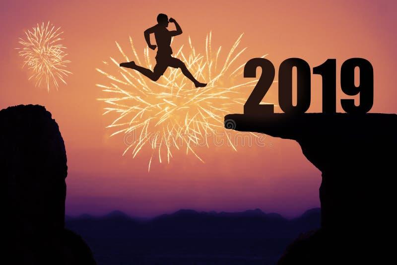 Feuerwerke bei Sonnenuntergang mit Schattenbild des neuen Jahres 2019 und springendem MA lizenzfreie stockbilder