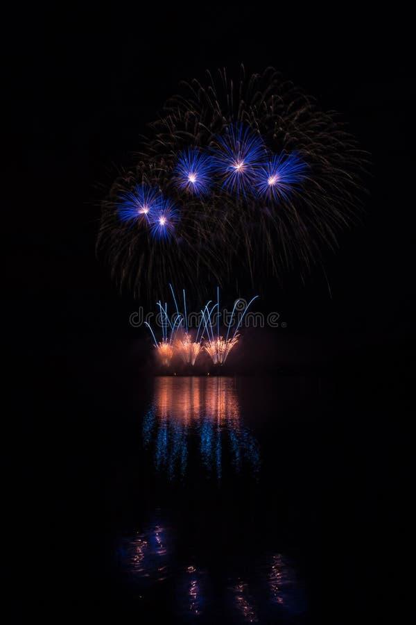 Feuerwerke des orange Brunnens und der blauen Sterne über Brnos Verdammung mit Seereflexion lizenzfreies stockbild