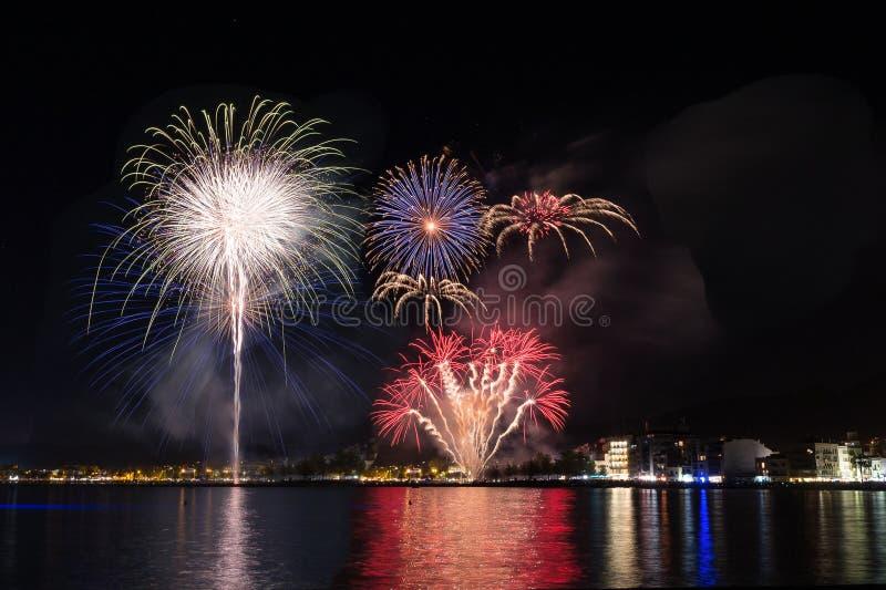 Feuerwerke, Feuerschloss in der Küste, Reflexion auf dem Meer nachts in den Rosen, Katalonien, Spanien lizenzfreies stockfoto