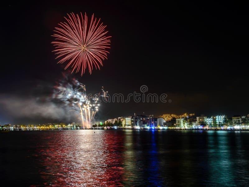 Feuerwerke, Feuerschloss in der Küste, Reflexion auf dem Meer nachts in den Rosen, Katalonien, Spanien stockfotografie
