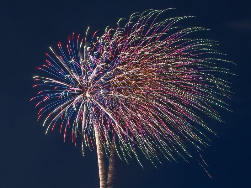 Feuerwerksexplosion im nächtlichen Himmel mit hellen Spuren stockbilder
