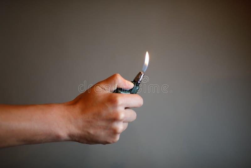 Feuerzeug, das durch eine Hand anzündet stockfotografie