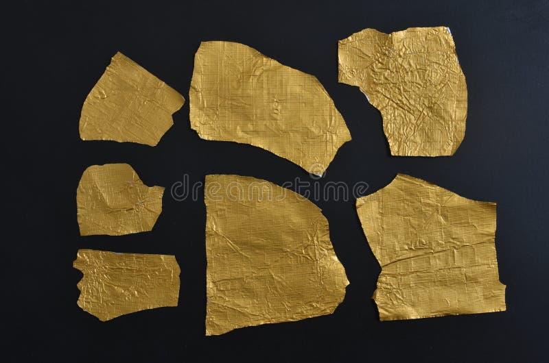 Feuille d'étain froissée d'or sur le fond noir image stock