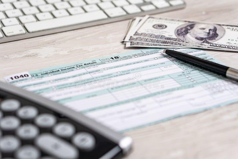 Feuille d'impôt des USA 1040 avec le stylo, la calculatrice et les billets d'un dollar concept blanc d'affaires du document Etats image libre de droits
