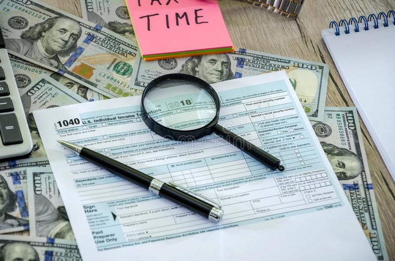 Feuille d'impôt 1040, dollars, bloc-notes et calculatrice sur une table en bois photos libres de droits