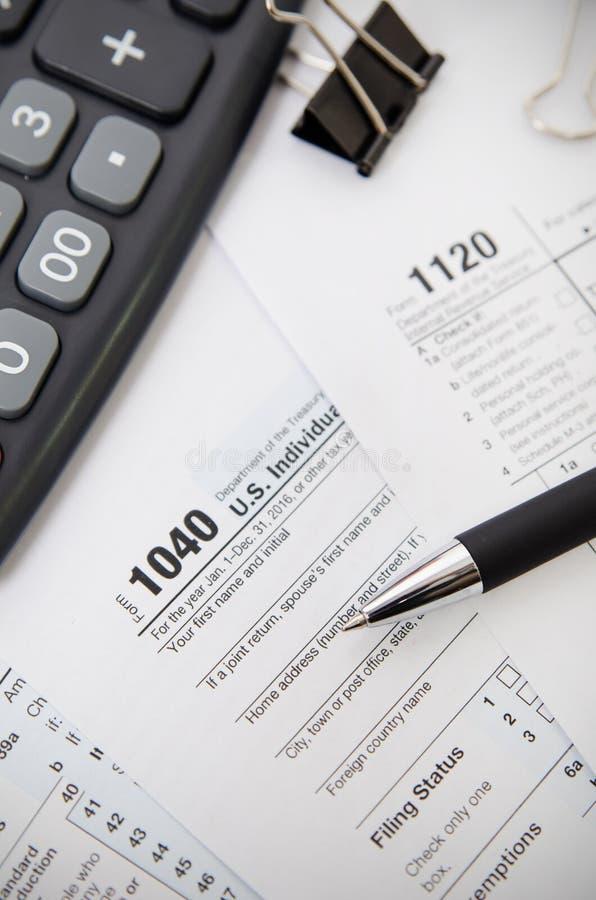 Feuille d'impôt des USA 1040 avec le stylo et la calculatrice images libres de droits