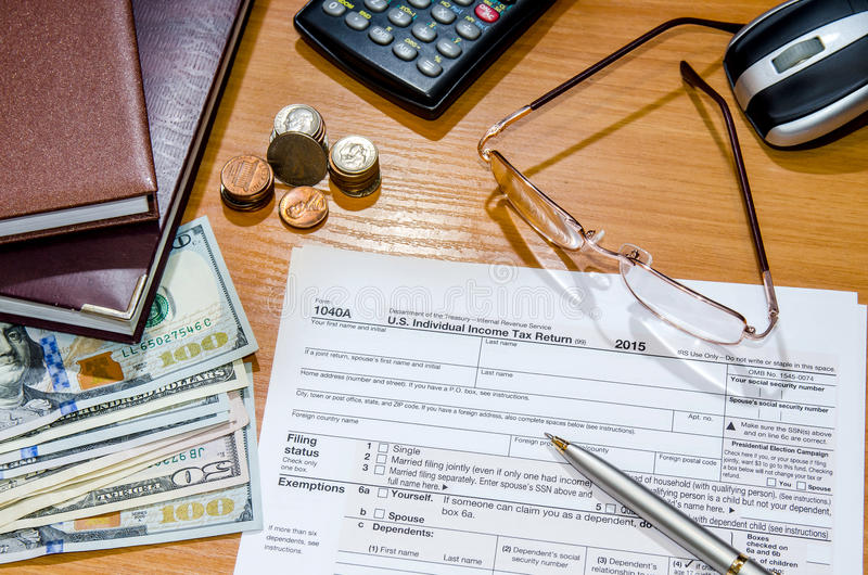 Feuille d'impôt 1040 pour 2016 avec le stylo, verres, dollars images libres de droits
