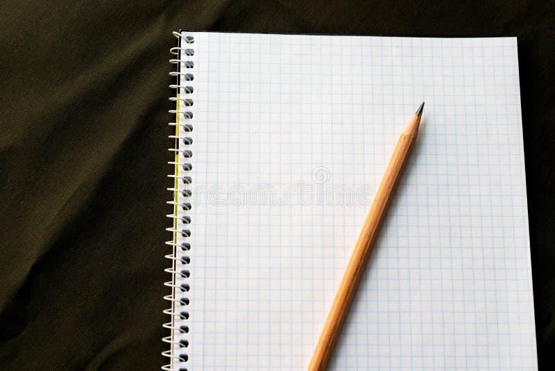 Feuille de carnet avec le crayon pour écrire la liste sur le fond des militaires images libres de droits