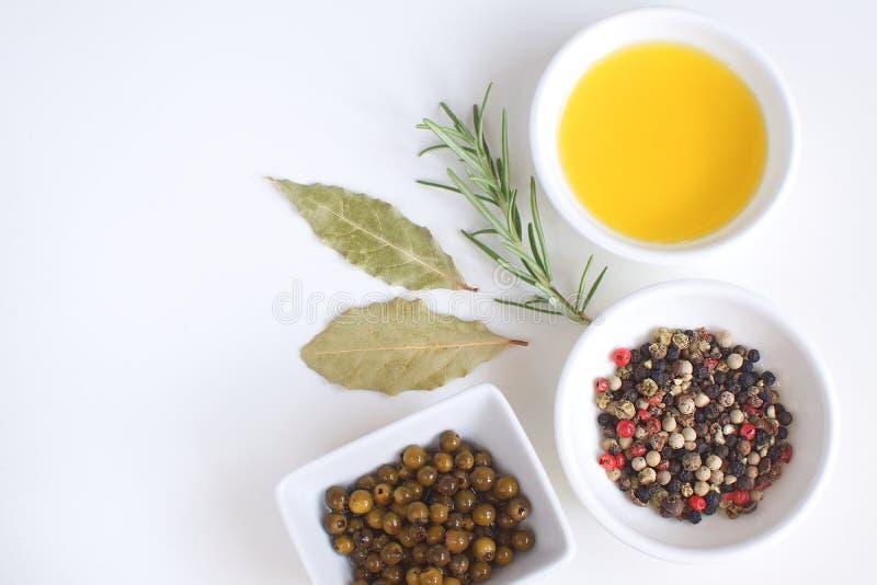 Feuille de laurier de préparation de poivre de branche de Rosemary de plat de porcelaine d'huile d'olive faisant cuire le fond bl images stock