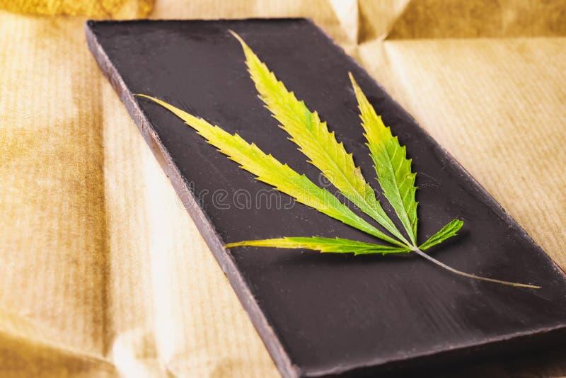 Feuille de marijuana avec le bloc foncé comestible de chocolat et 'brownie' de cannabis avec la vue supérieure de ganja sur le fo photographie stock libre de droits