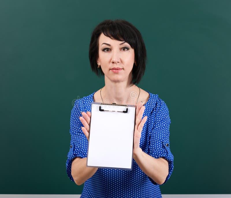 Feuille de papier blanc d'exposition d'étudiante près de panneau de craie, concept d'éducation, fond vert, tir de studio images stock
