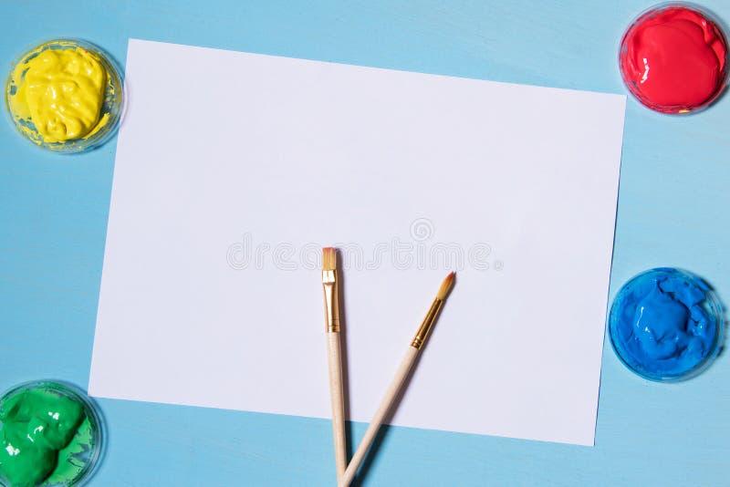 Feuille de papier blanche sur un fond bleu, une peinture rouge colorée de jaune de vert bleu et un endroit de brosse pour l'espac photographie stock