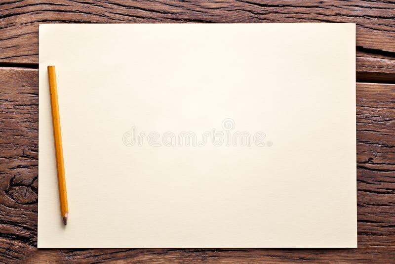 Feuille de papier et de crayon sur la vieille table en bois. photo stock