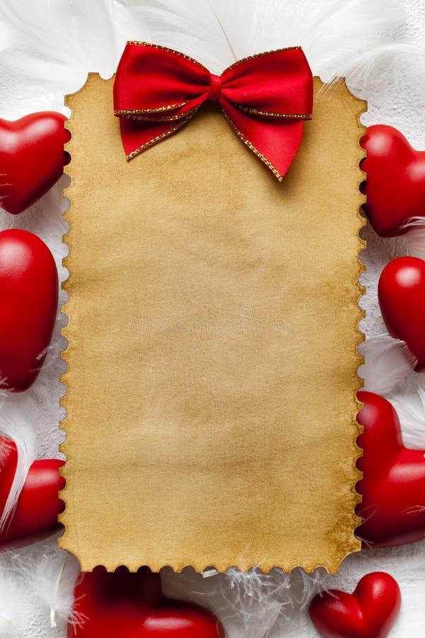 Feuille de papier faite main de blanc, arc rouge et coeurs rouges photographie stock