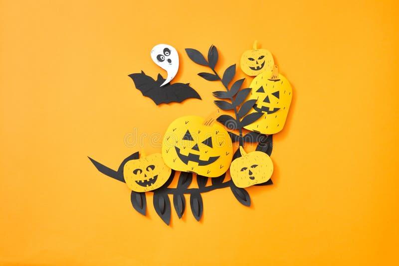 Feuilles, batte de vol, fantôme et potiron avec un visage effrayant sur un fond orange avec l'espace pour le texte Papier de méti photos libres de droits