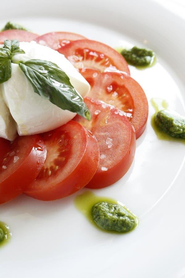 Feuilles découpées en tranches de tomate, de mozzarella, de pesto et de basilic sur un platin gastronome photos stock