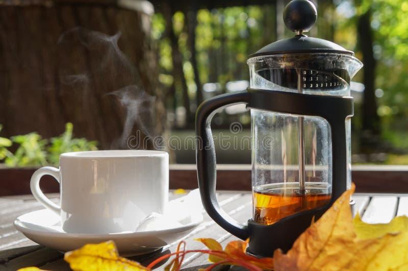 Feuilles d'automne et une tasse chaude de cuire le thé à la vapeur Table en bois contre le jour froid ensoleillé sur un fond natu photos libres de droits