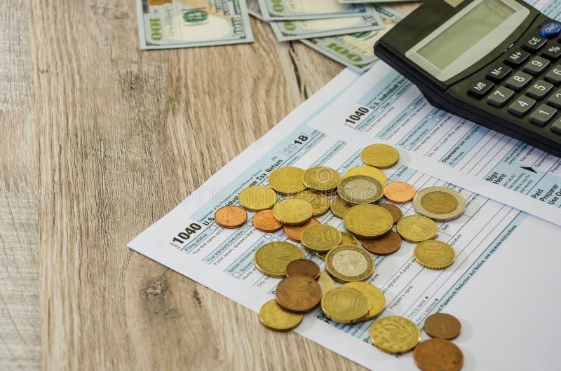 Feuilles d'impôt 1040, calculatrice et dollars sur un fond en bois, en gros plan photos libres de droits