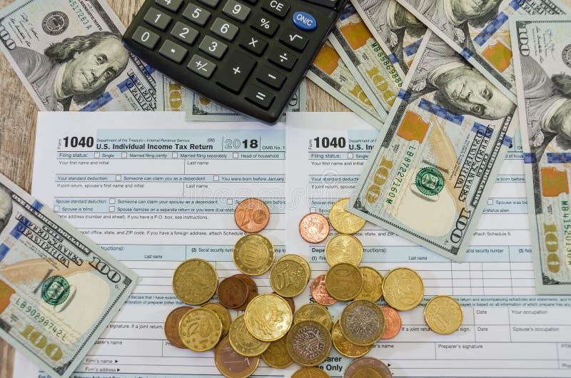 Feuilles d'impôt 1040, calculatrice et dollars sur un fond en bois, en gros plan image libre de droits