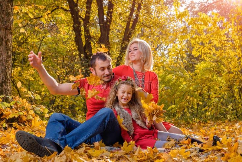 Feuilles de lancement de jeune famille blanche dans le jour ensoleillé d'automne image stock