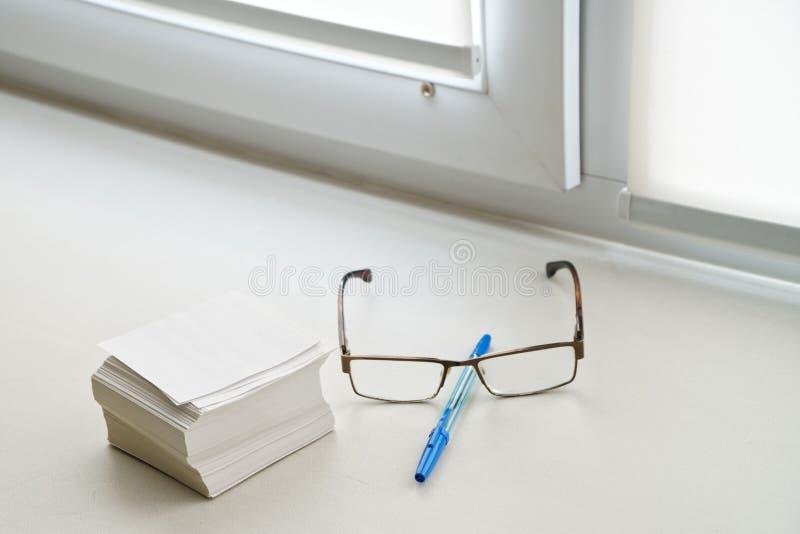 Feuilles de note, verres et un mensonge de stylo sur le rebord de fenêtre dans le bureau photo stock