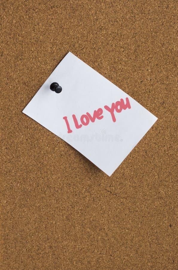 Feuilles de papier avec une déclaration de l'amour sur un fond de liège photos stock