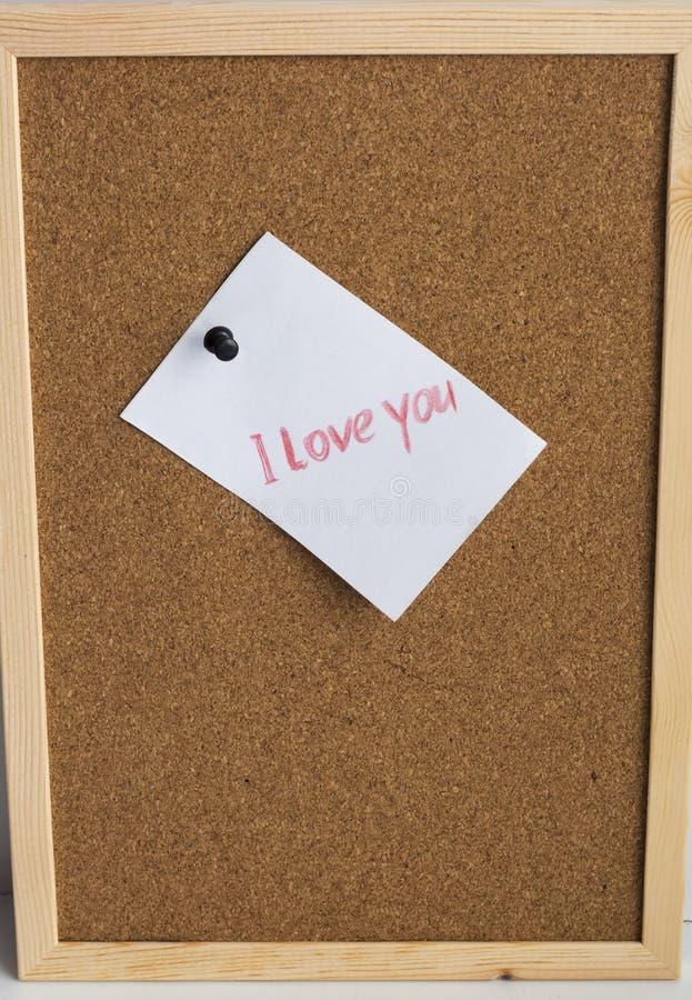 Feuilles de papier avec une déclaration de l'amour sur un fond de liège photo stock