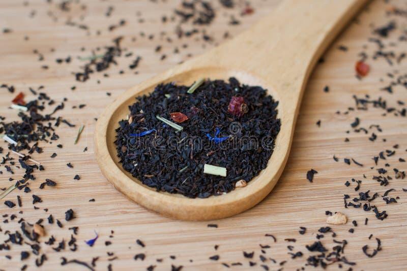 Feuilles de thé et thé sec sur une cuillère en bois sur un backgroun en bois photo libre de droits