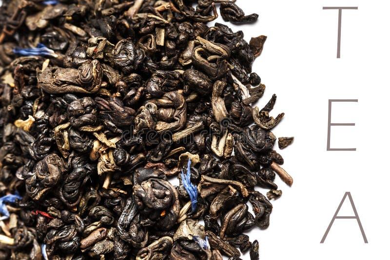 Feuilles de thé noires sèches d'isolement sur une fin blanche de fond vers le haut de W image libre de droits