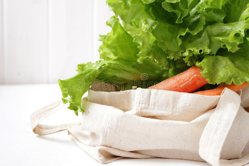 Feuilles et carotte de laitue dans un sac de toile sur la table blanche photographie stock