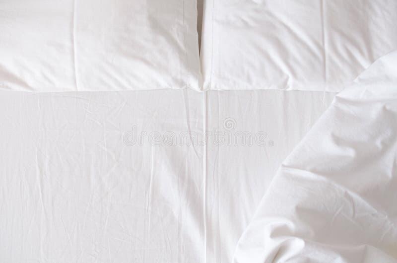 Feuilles et oreillers blancs de literie photographie stock