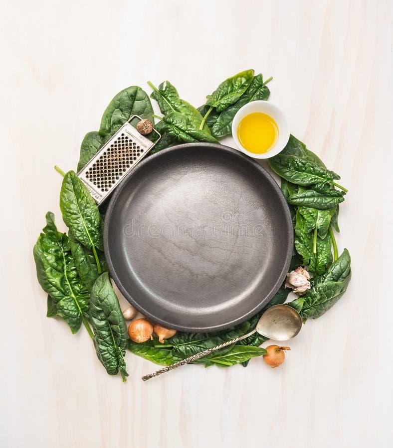 Feuilles fraîches d'épinards avec faire cuire des ingrédients : huile, noix de muscade, ail et olnion autour d'un plat gris vide  images libres de droits