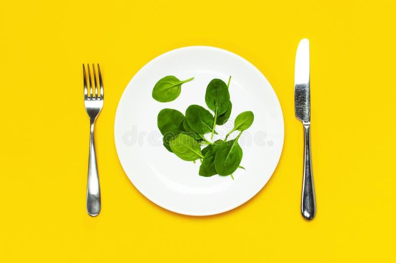 Feuilles vertes fraîches d'épinards sur un couteau blanc de fourchette de plat sur l'espace de copie étendu par appartement jaune images libres de droits