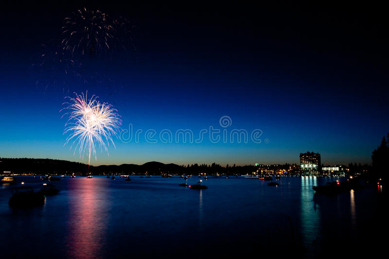Feux d'artifice au-dessus de lac au crépuscule photo stock
