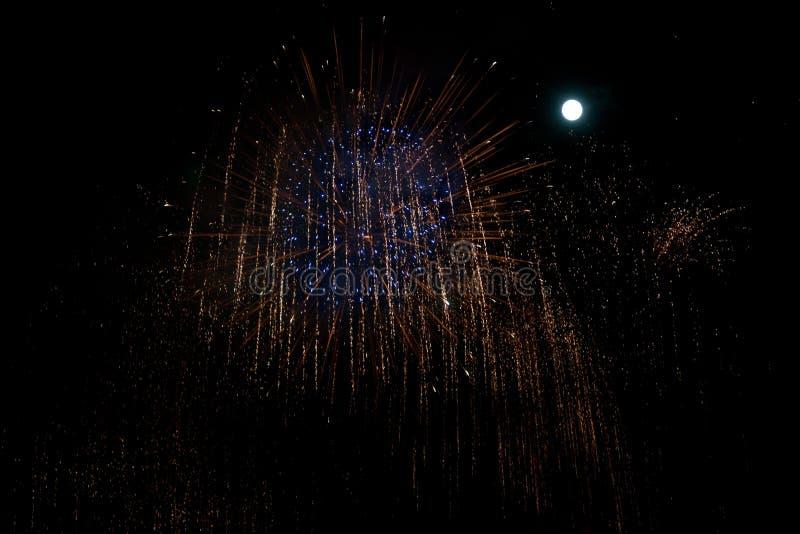 Feux d'artifice bleus et rouges au fond de nuit avec la lune photos stock