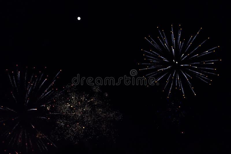 Feux d'artifice colorés et cierges magiques blancs sous une pleine lune lumineuse photographie stock