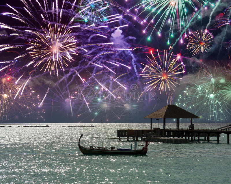Feux d'artifice de fête au-dessus de la mer et d'une silhouette de bateau sur l'eau maldives photographie stock