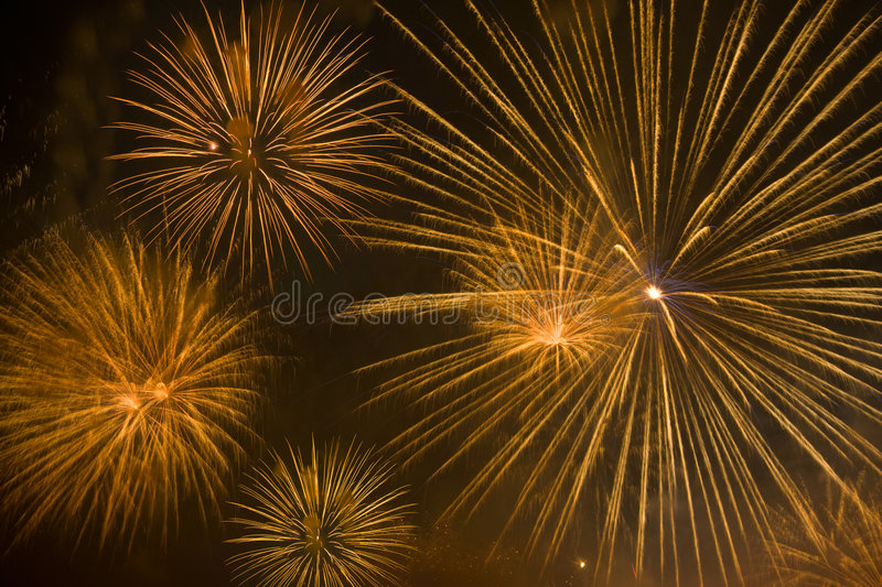 Feux d'artifice oranges en ciel de nuit images stock