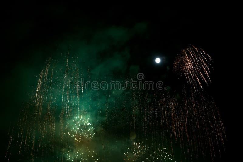 Feux d'artifice verts et d'or au fond de nuit avec la lune images stock