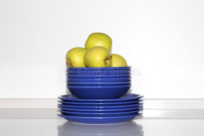 Few żółci jabłka są na błękitnych talerzach Mnóstwo talerze obraz royalty free