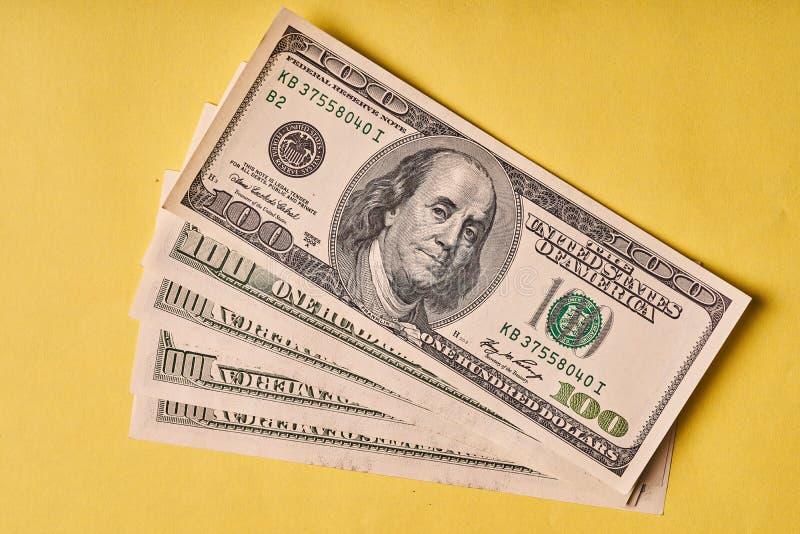 Few Amerykańscy dolary na papierowym żółtym tle fotografia stock