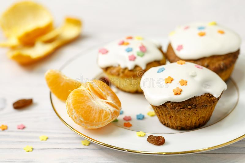 A few appetizing muffins and slices of mandarin lie on a plate royalty free stock images