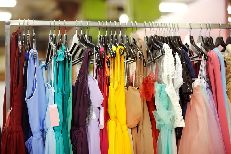 Few beautiful bridesmaid or evening dresses or ball gown on a hanger in a bridal shop royalty free stock photo
