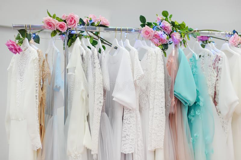 Few beautiful wedding, bridesmaid or evening dresses or ball gown on a hanger in a bridal shop. Few beautiful wedding, bridesmaid or evening dresses ball gown on stock photos