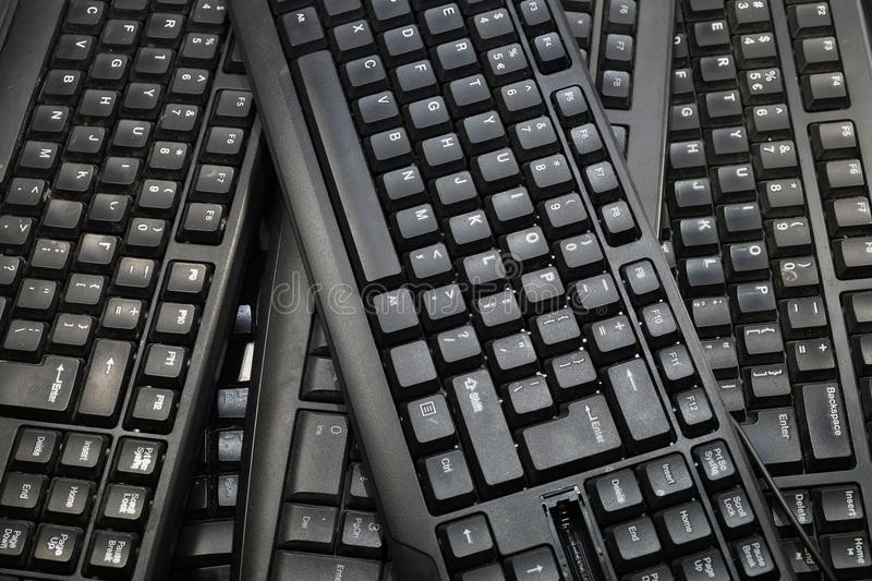 A few black computer keyboards. Horizontal frame. Horizontal frame filled with black computer keyboards. Computer equipment used for recycling stock photo