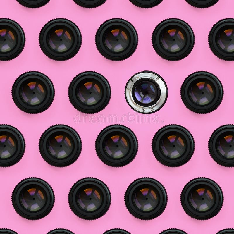 A few camera lenses with a closed aperture lie on texture background of fashion pastel pink color paper in minimal concept. royalty free stock photography