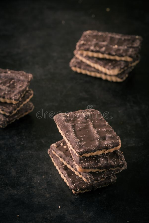 Few chocolate biscuits in stack on dark tray. Vertical photo with few stacks of square biscuits with chocolate on one side. Each stack consists of four or free royalty free stock image