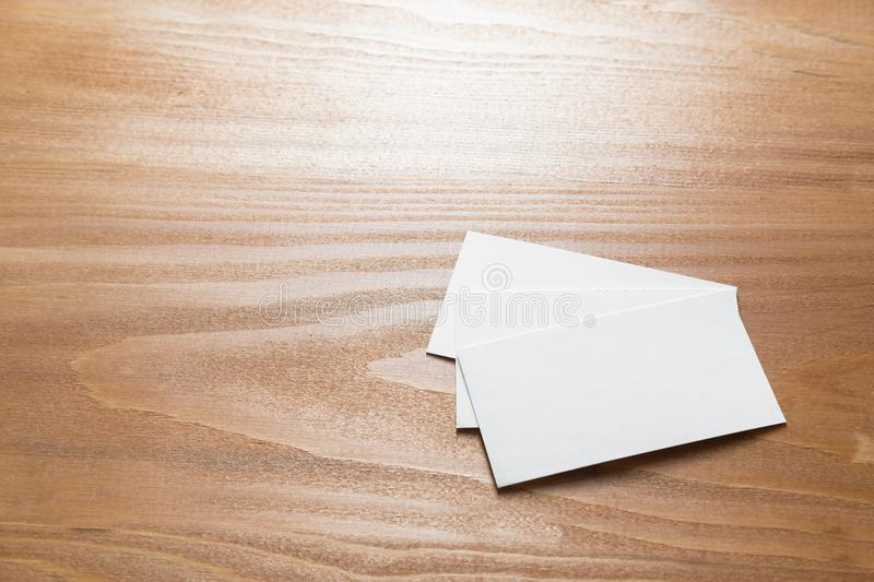 Few clean white business cards with space for text. Several clean white business cards with space for text on a light wooden surface stock image